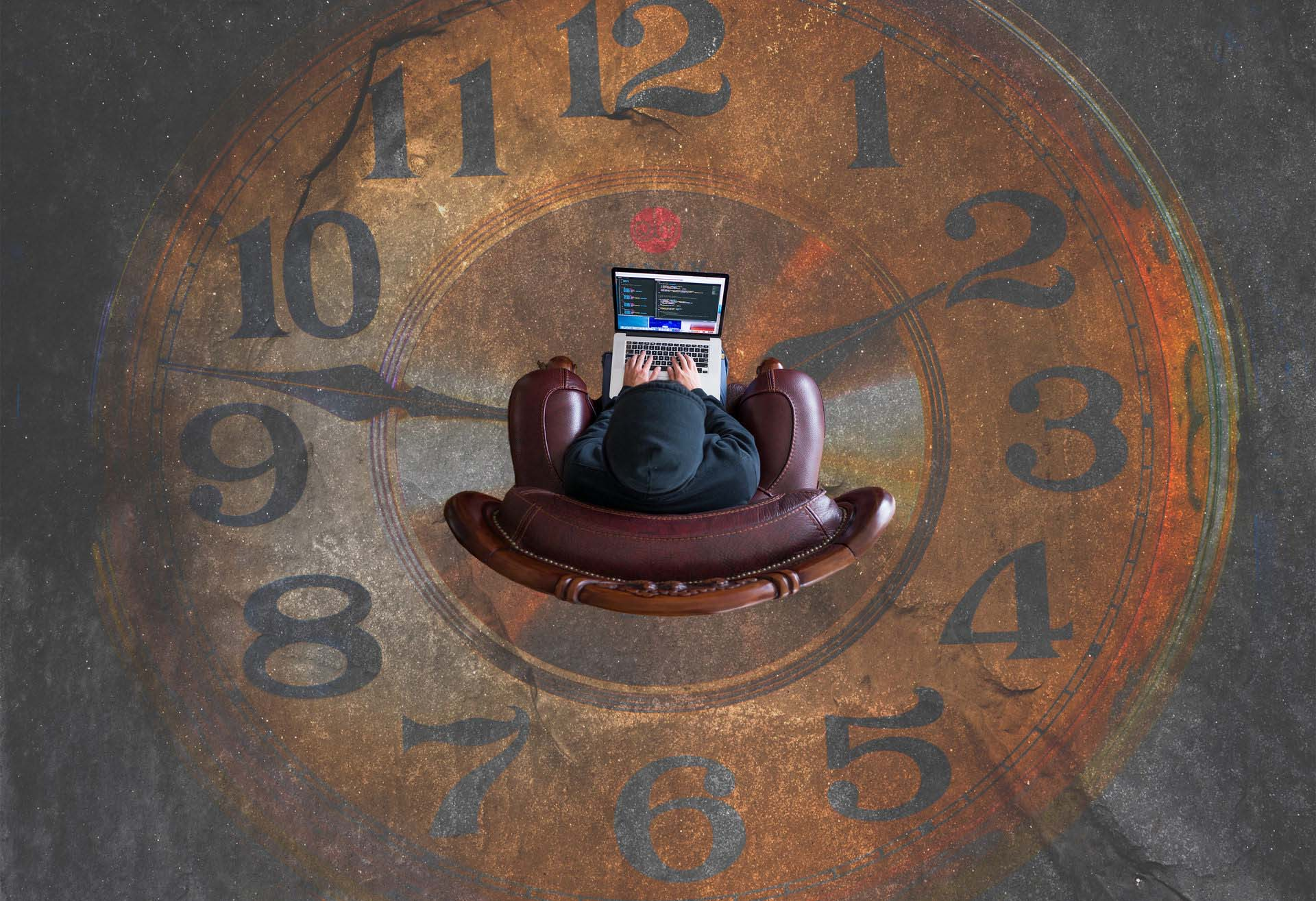 Aerial photo of customer in a chair using a laptop over a large clock representing customer lifetime value