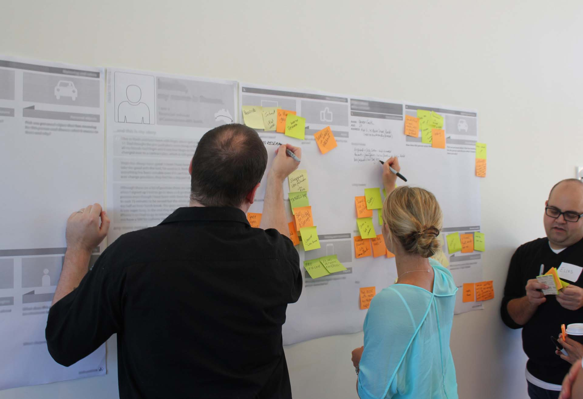 Three Proto employees making notes on a Customer Journey Map