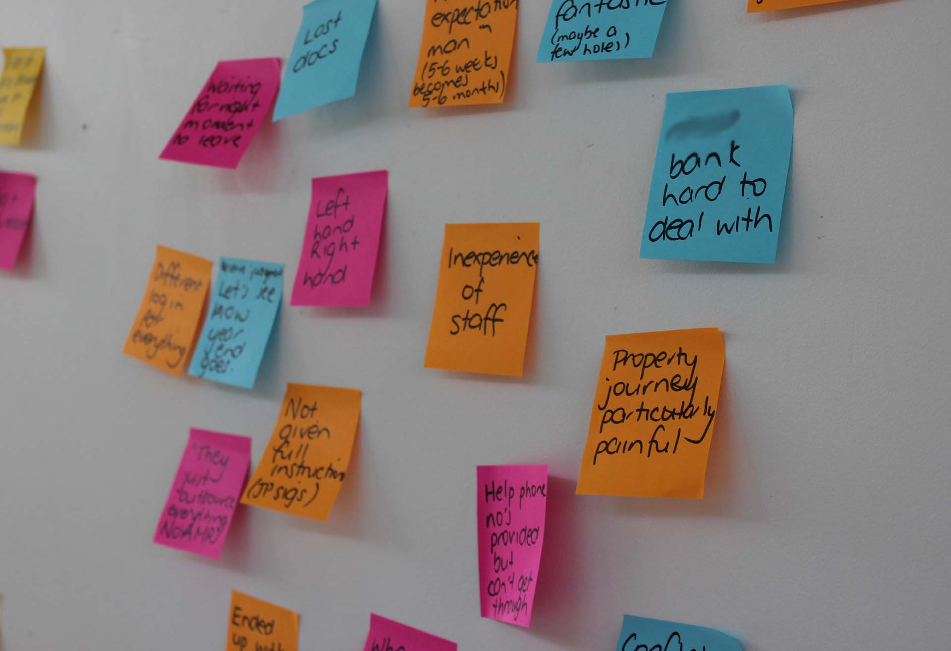 Coloured Promoter & Detractor customer experience notes on a wall