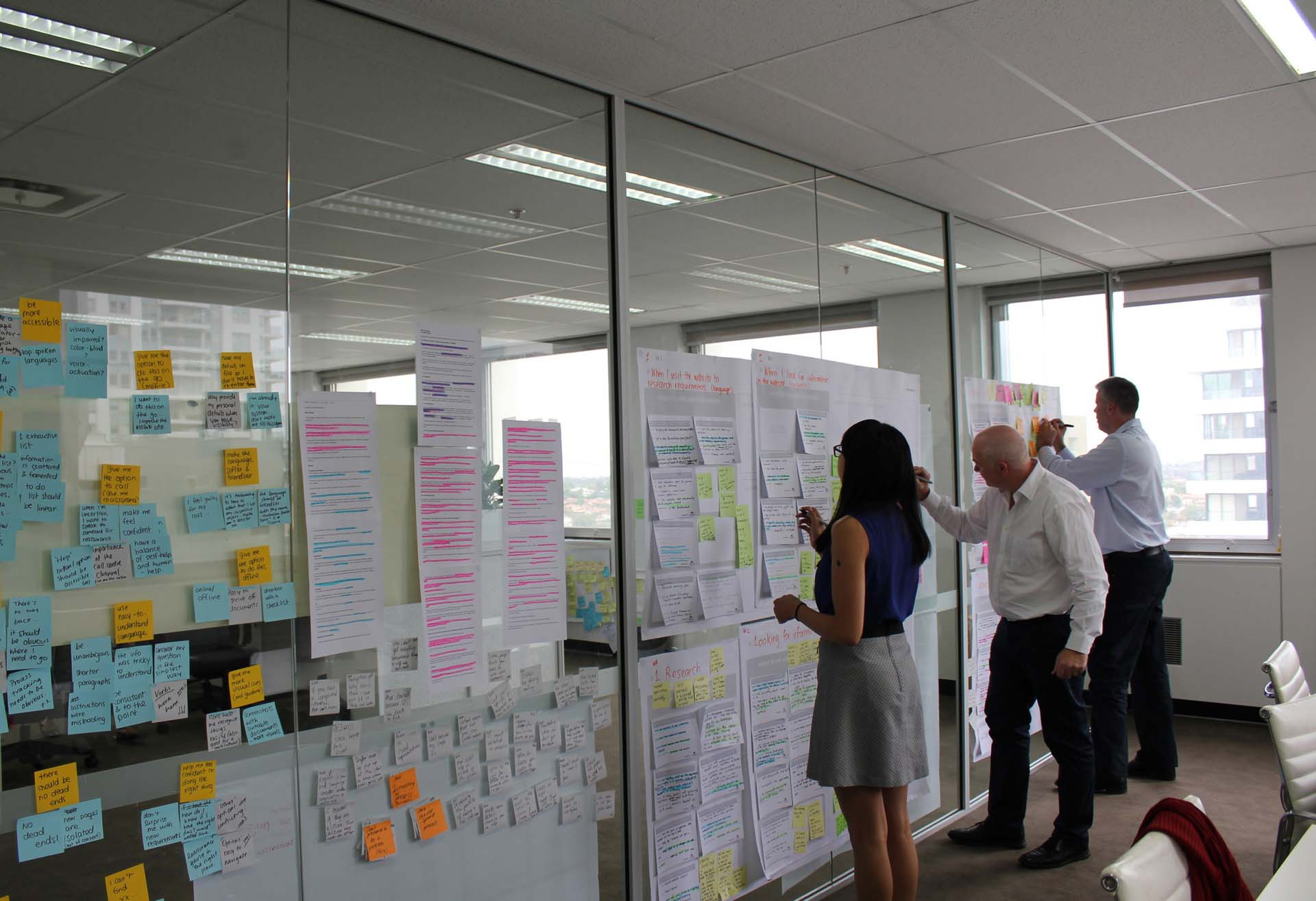 Three Proto employees making notes on a large Customer Journey Map