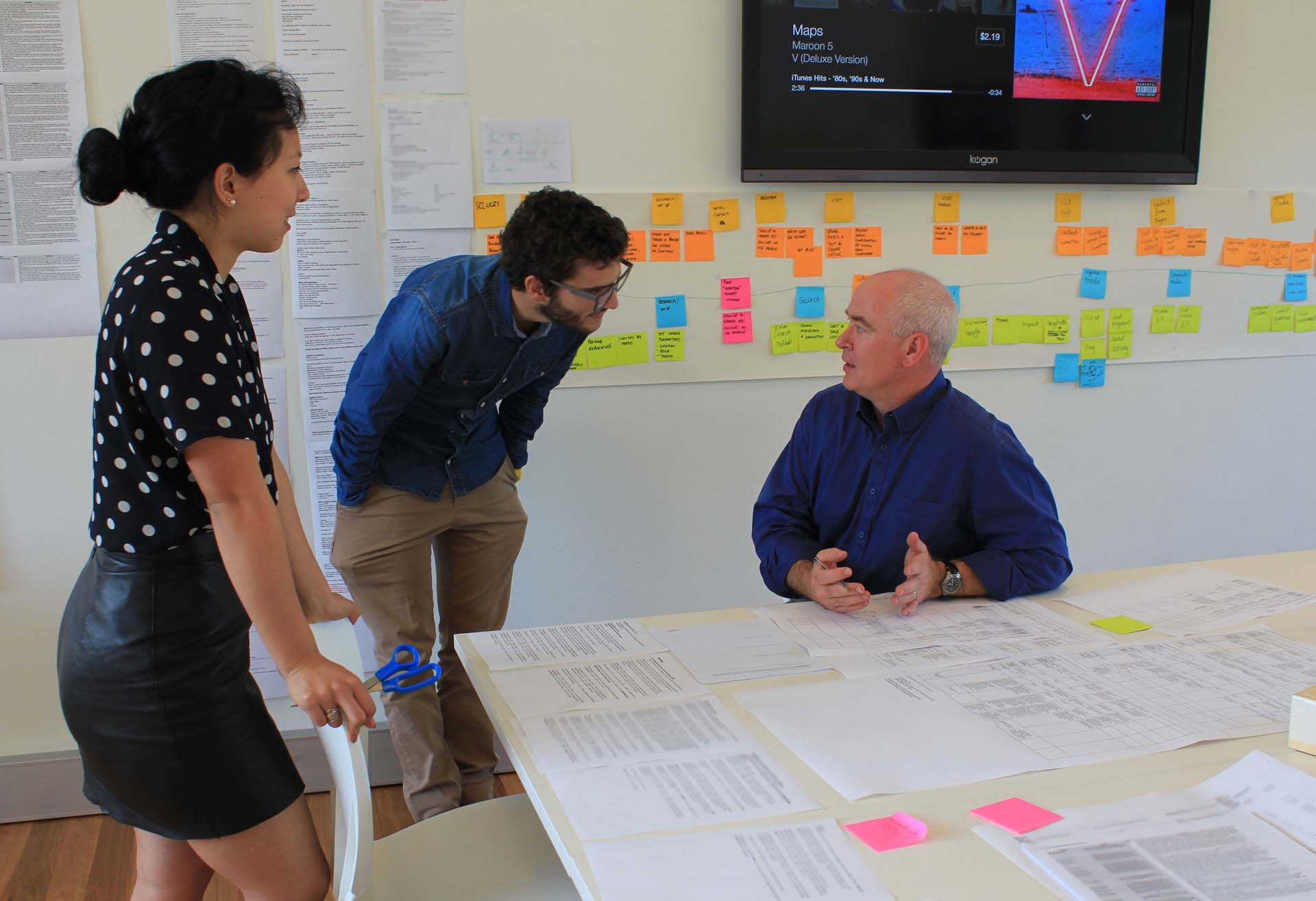 Proto experience designers discussing a customer journey map