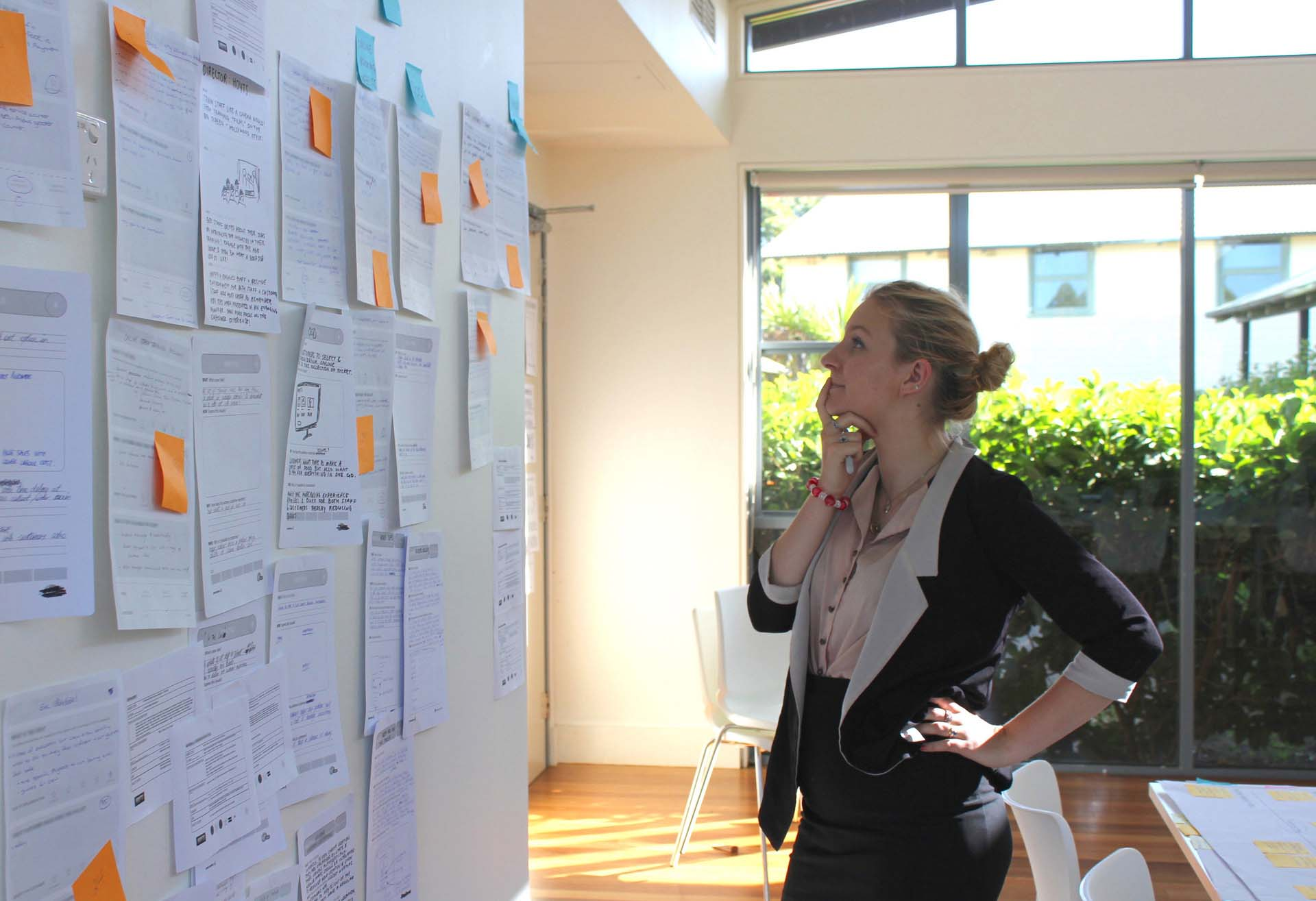 Woman thinking about a wall of Service Design information