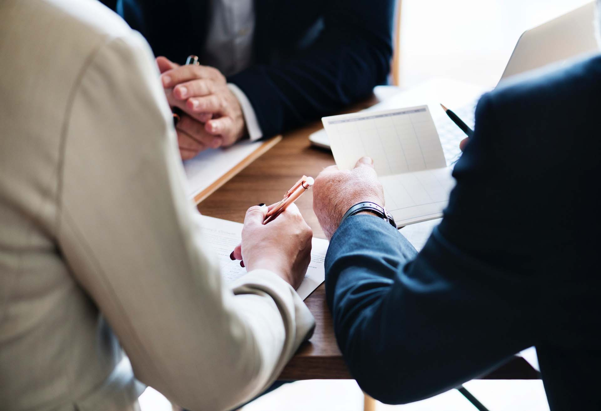 Three people looking at documents in a business meeting