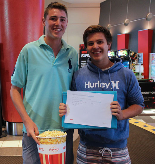 Hoyts customers holding a bucket of popcorn and a customer feedback form