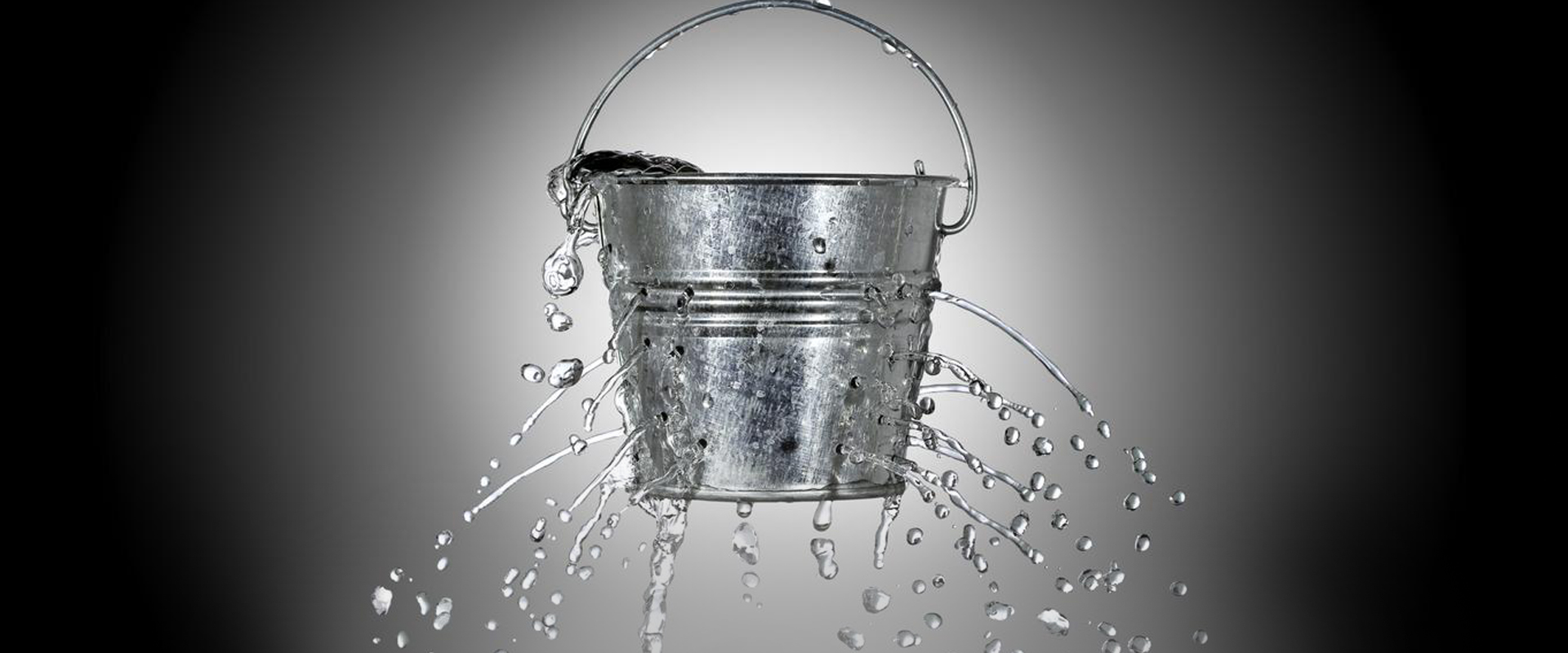 A bucket which is leaking due to many holes punctured in its metal.