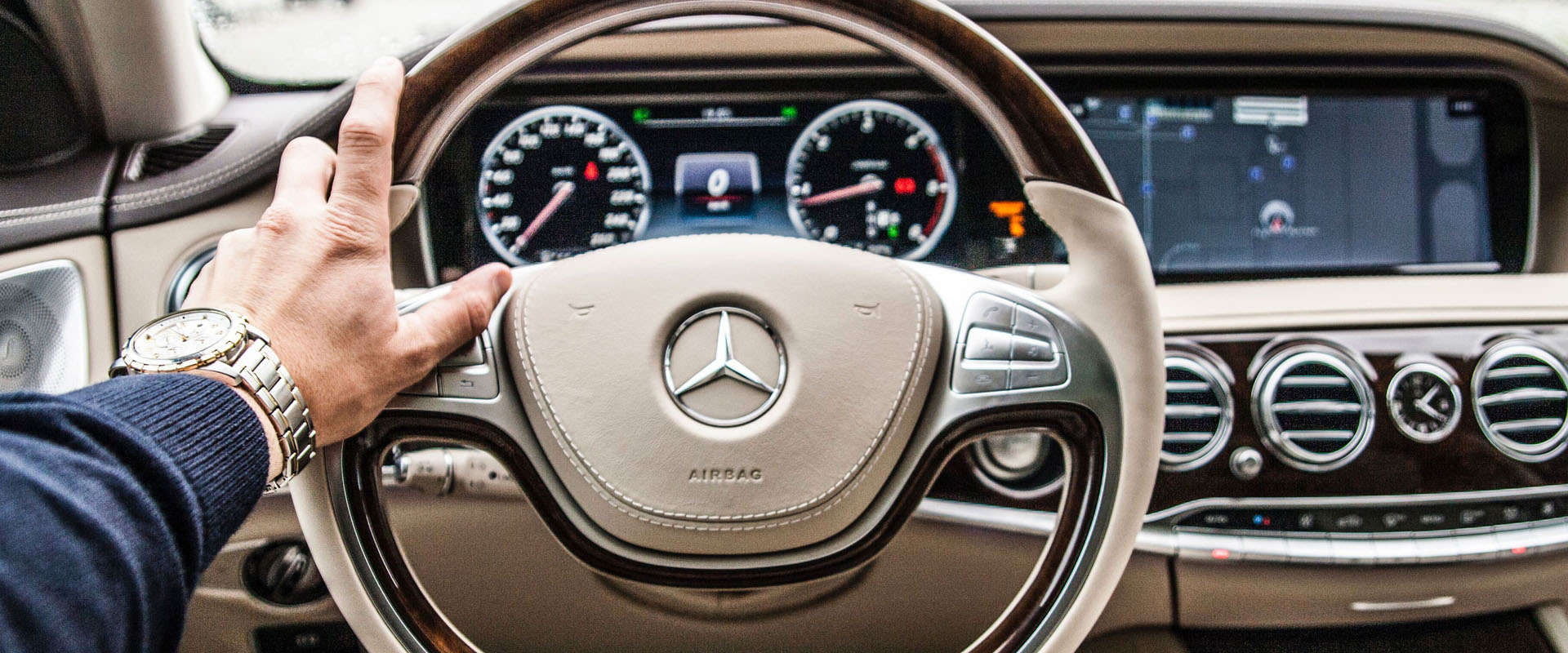 Hand on a Mercedes Benz steering wheel