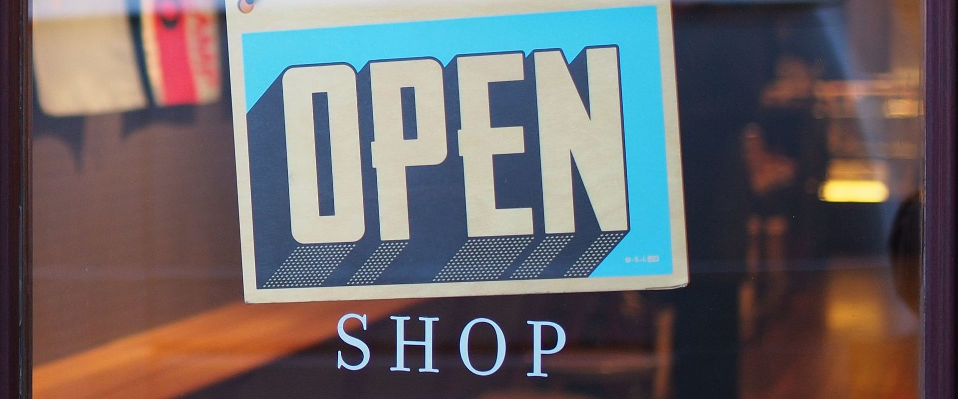 Open sign in a retail shop front window representing the creation of a remarkable retail shopping experience