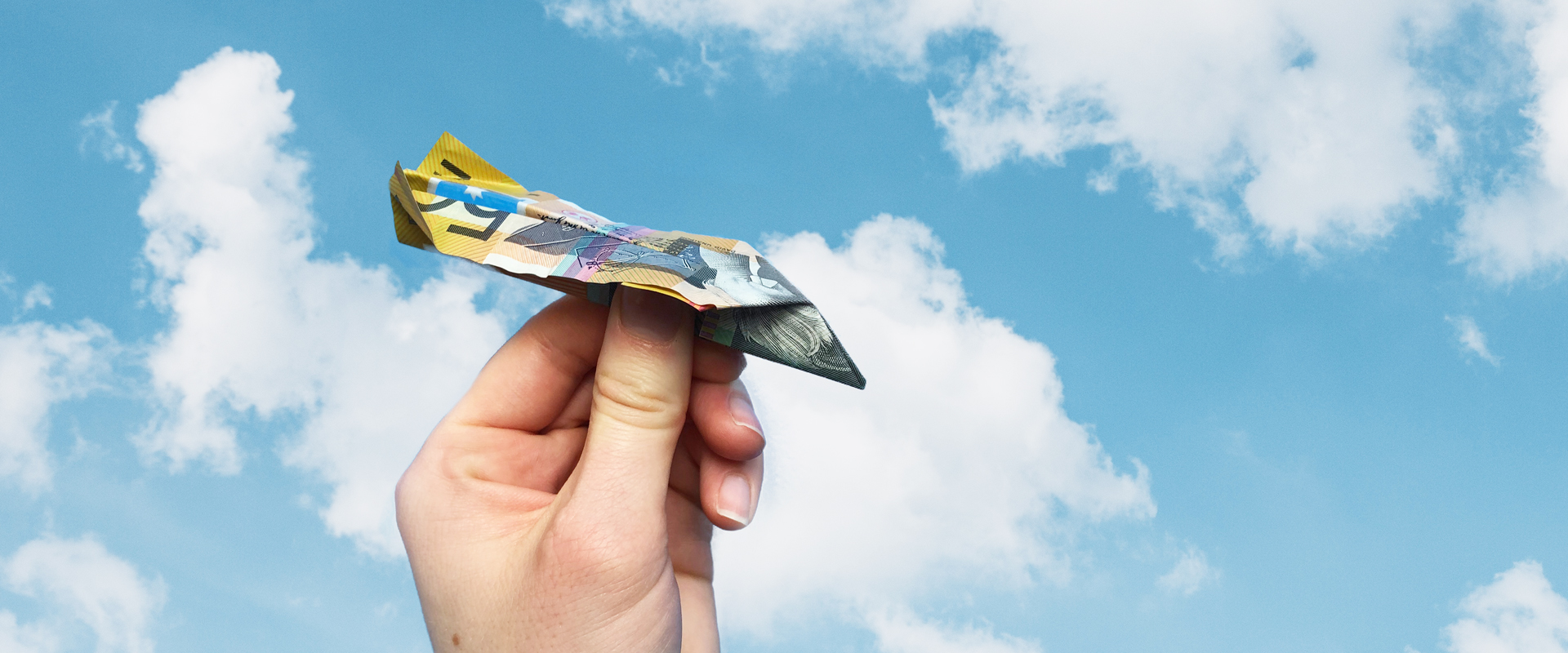 hand holding an AU$50 banknote paper aeroplane against a blue sky