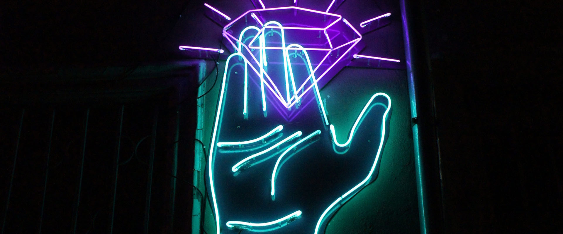 Neon sign of a hand capturing a diamond representing the brilliant basics