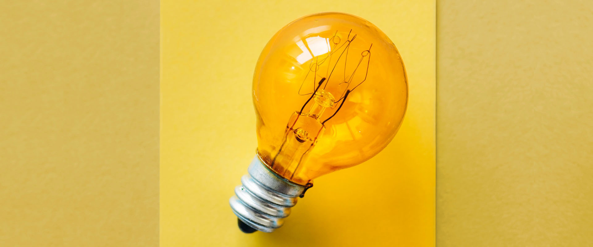 Orange light bulb on a yellow background representing thinking and innovation