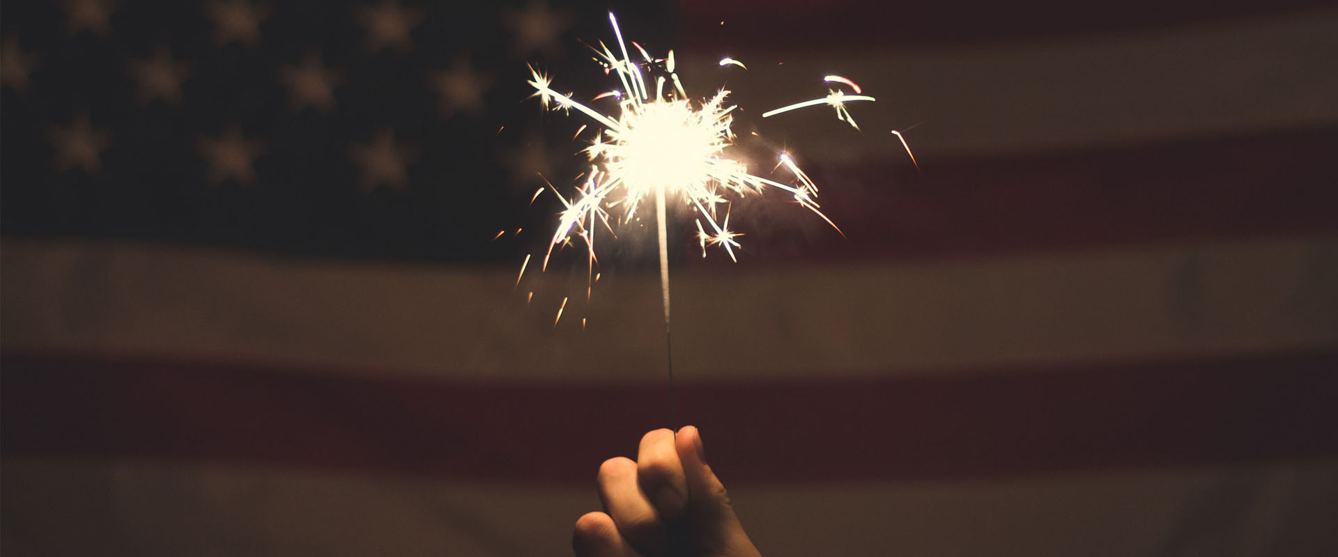 Sparkler in front of an American flag representing Service Design delight