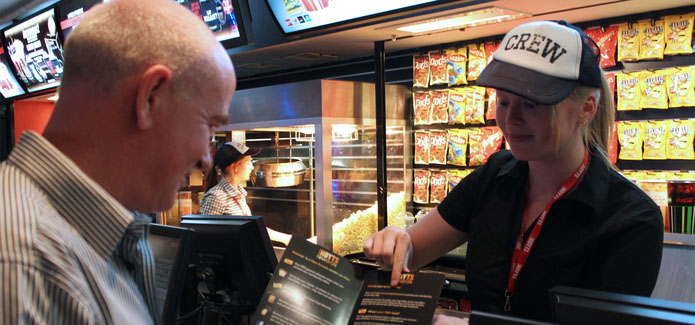 Hoyts employee pointing out menu items to a customer