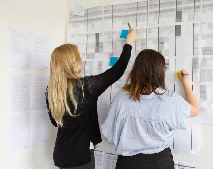 Two Proto experience designers working on a customer experience journey map