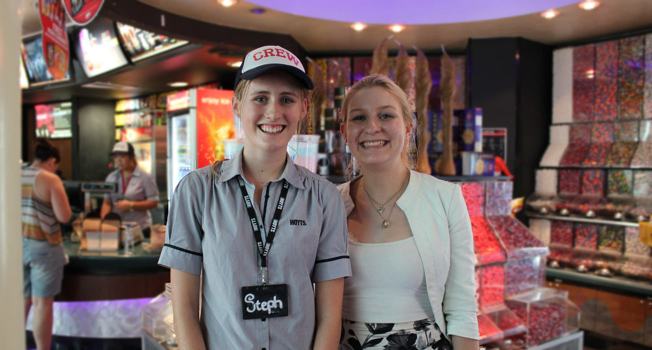 Two smiling Hoyts employees in front of the candy bar